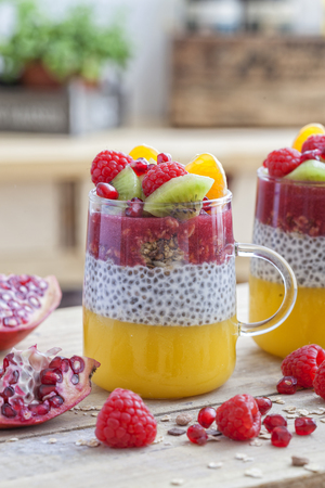 Healthy dessert in a glass with chia seeds, mango, cereals, raspberry and kiwi.
