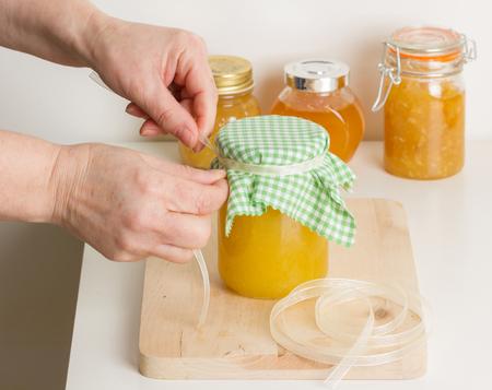 A woman making homemade marmalade and closing the jar tying the ribbon.