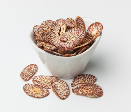 Betel nut chips in a bowl on a white surface.