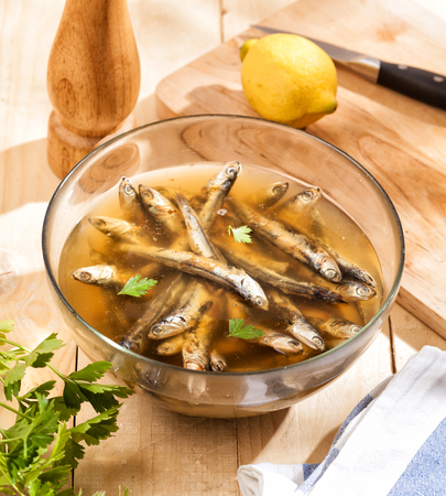 Preparing a marinade for sardines with lemon and pepper.