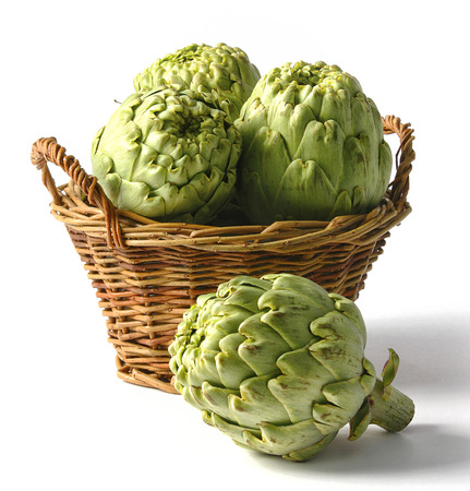 Homegrown artichokes in a basket on a white surface.