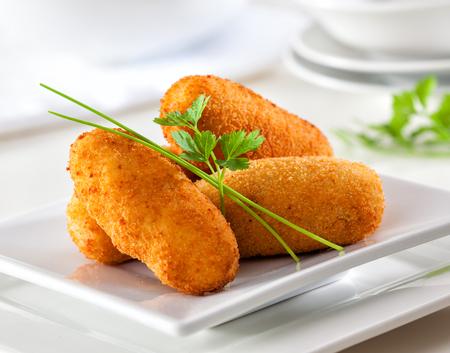 Croquetes gourmet caseiros deliciosos na placa branca.