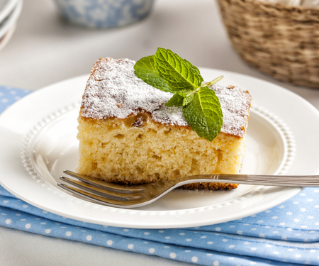 Slice of homemade cake with powdered sugar and mint leaves Banco de Imagens