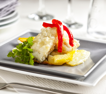 Fried cod served with potatoes, egg and bell pepper. Stock Photo