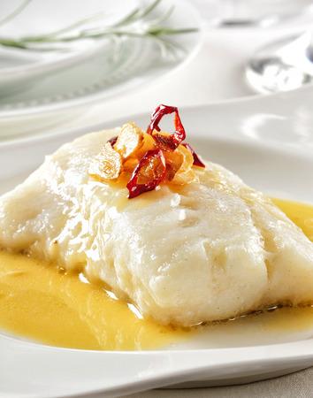 Cod prepared with garlic, chili pepper and olive oil. Stock Photo