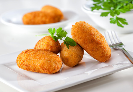Homemade gourmet croquettes on a white plate with fork. 스톡 콘텐츠
