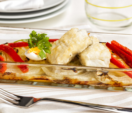 Fried cod served on a tray with onions and bell pepper. Stock Photo