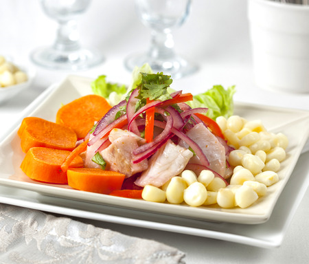 Ceviche, typical dish from Peru. Served with sweet potato, corn and onions. Imagens