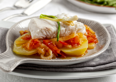 Fish fillet served with potatoes, tomato, bell pepper and onions. Stock Photo