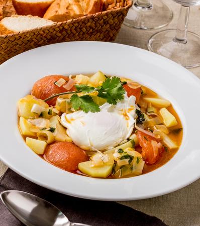 Soup with potato, tomato and poached egg.
