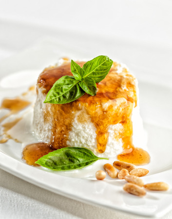 Fresh cottage cheese with honey and pine seeds. Banco de Imagens