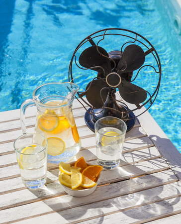 Refreshing water with ice, lemon and orange and a vintage fan on a hot summer day. Banque d'images