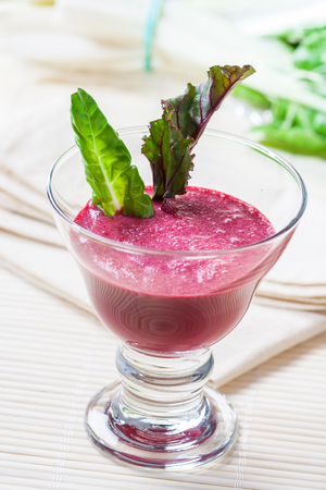 A red beetroot smoothie in a glass, garnished with beetroot and lettuce leaves.