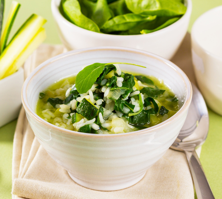 A bowl with rice, spinach and zucchini, served like a soup.