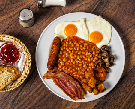 A full English breakfast is a breakfast meal that typically includes bacon, sausages, eggs, tomato, beans and a beverage such as coffee or tea. Reklamní fotografie