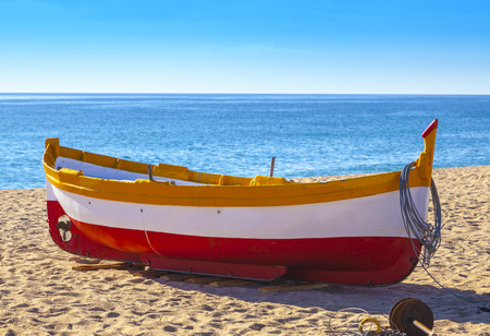Fishing boats rest on a golden sand beach overlooking the blue sea. Reklamní fotografie