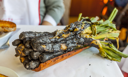 Calcotada, typical Catalan tradition. Calcot onions from the barbecue served in terra cotta tiles. Imagens