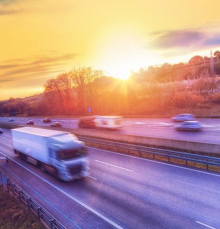 Heavy truck speeding on highway at sunset. Motion blur. Stock Photo