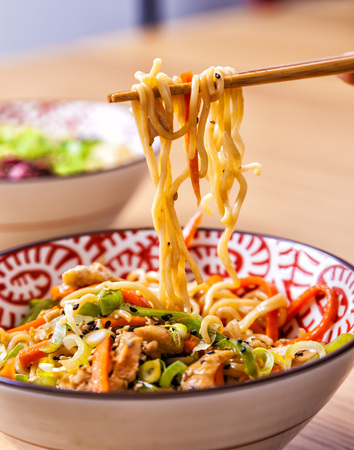 Japanese noodles in a bowl with vegetables and chopsticks. Stock Photo