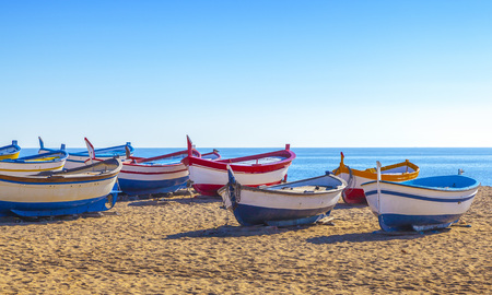 Fishing boats rest on a golden sand beach overlooking the blue sea. Imagens