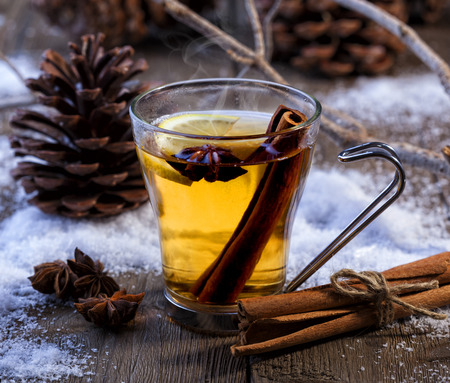 Hot winter beverage with cinnamon, anise and lemon. Winter scene with pine cones and snow. Zdjęcie Seryjne