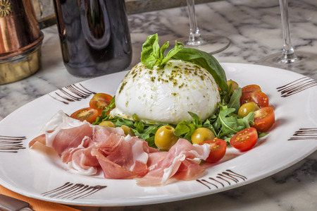 Nothing compares to the taste of a fresh buffalo mozzarella with basil, rucula and freshly sliced parma ham. Foto de archivo