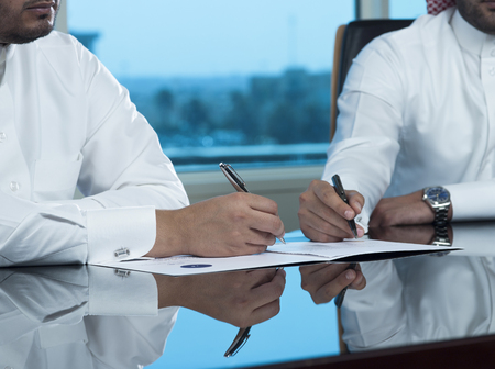 Two Saudi Businessmen Hands Signing a document, contract or making a deal