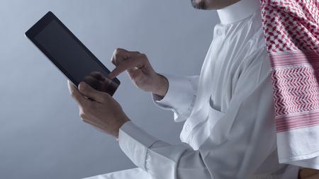 Saudi Arabian Man Hands Holding and Using Tablet Stock Photo