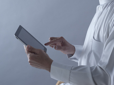 Saudi Arabian Man Hands Holding and Using Tablet Stock Photo