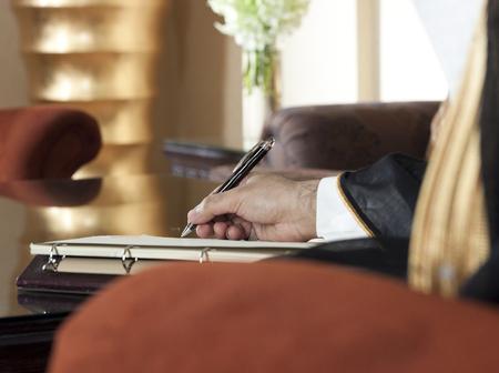 Saudi Arabian Man Hand Writing on A Notebook in a Luxury Home Environment, wearing Saudi Thob, Ghutra and Black Bisht