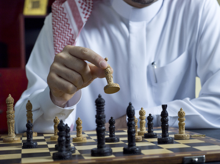 An Arab man playing chess at his desk Stock Photo
