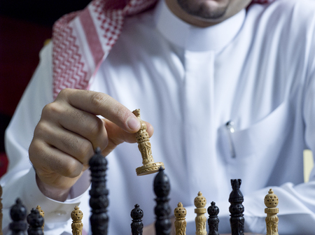 An Arab man playing chess at his desk Stock Photo