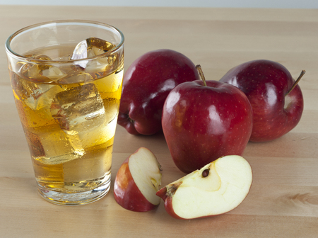 A Glass of Fresh Cold Apple Juice with Ice Beside Apples on A Wooden Table Background Stock Photo