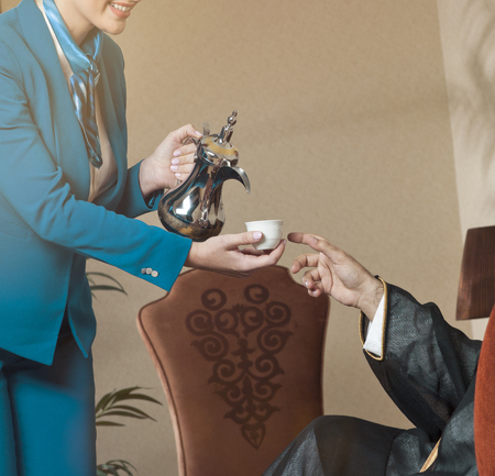 Waitress Serving Arabic Coffee to a Wealthy Saudi Arab Man