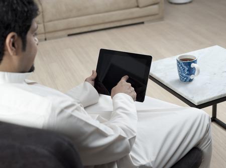 Saudi Arabian Man Using Tablet at Home Environment Stock fotó