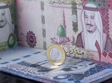 Saudi Riyal Coin Standing on Top of Banknotes