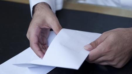 Businessman hands opening an envelope