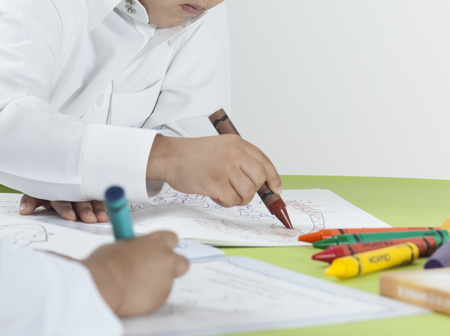 Kids drawing with colored crayons on paper at a table Stock Photo