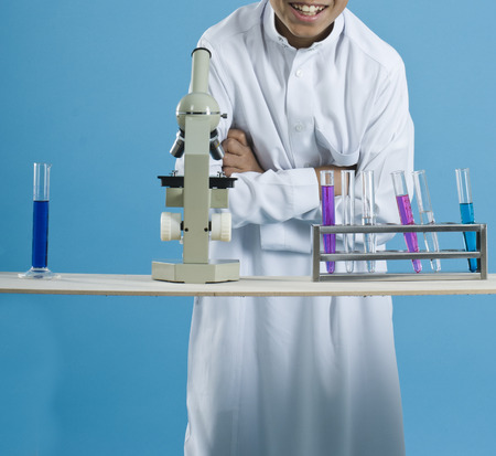 School boy using a microscope with colorful chemicals in test tubes