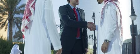 Nahöstliche und kaukasische Geschäftsleute, die an einem sonnigen Tag Hände im Freien schütteln Standard-Bild