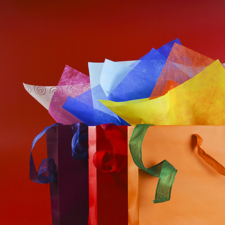 Colorful shopping bags with colorful wrapping papers and ribbons still life Reklamní fotografie