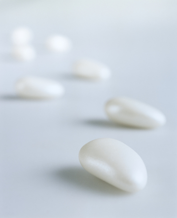 White candy-coated almonds still life composition imitating steps