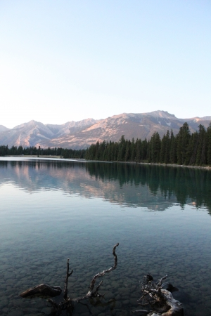tinge: The last remaining daylight gives this mountain a beautiful reddish tinge and the lake a dark yet still clear blue  Photo taken in Jasper National Park, Canada Stock Photo