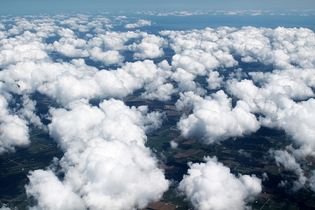 cirrus: A sky full of clouds as seen from above with countless fields underneath and a lake in the background Stock Photo