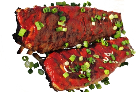 Two racks of bbq ribs garnished with a delicious barbeque sauce and topped with freshly cut green onions photo