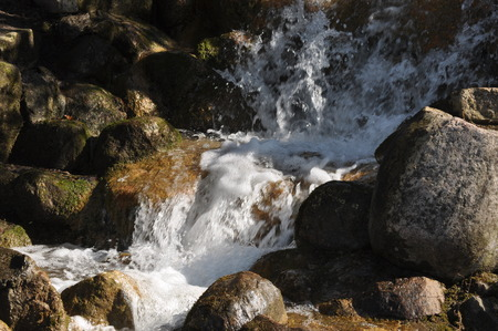 rapidly: Rapidly flowing water near a waterfall on a sunny day Stock Photo
