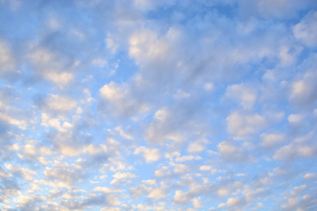 white, pink and gray clouds in autumn evening sky just before sunset