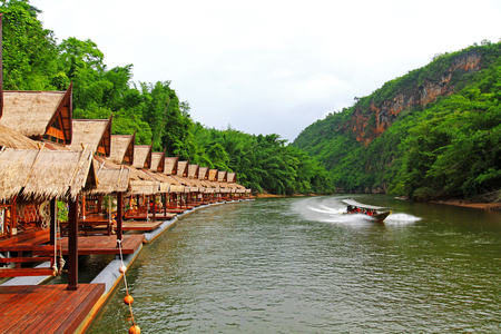 Many wooden house floating on the river with mountain and speed boat at Float house river kwai resort, Kanchanaburi, Thailand