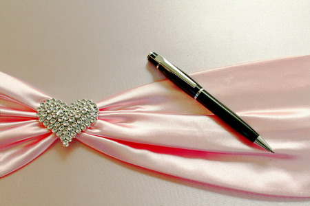 Diamond heart and black pen with pink bow on the book. write, memo memorial, diary, congratulatory and wedding book concept