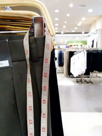 Waist tape hanging from men's slacks with copy space and light blurred background at men fashion shopping store